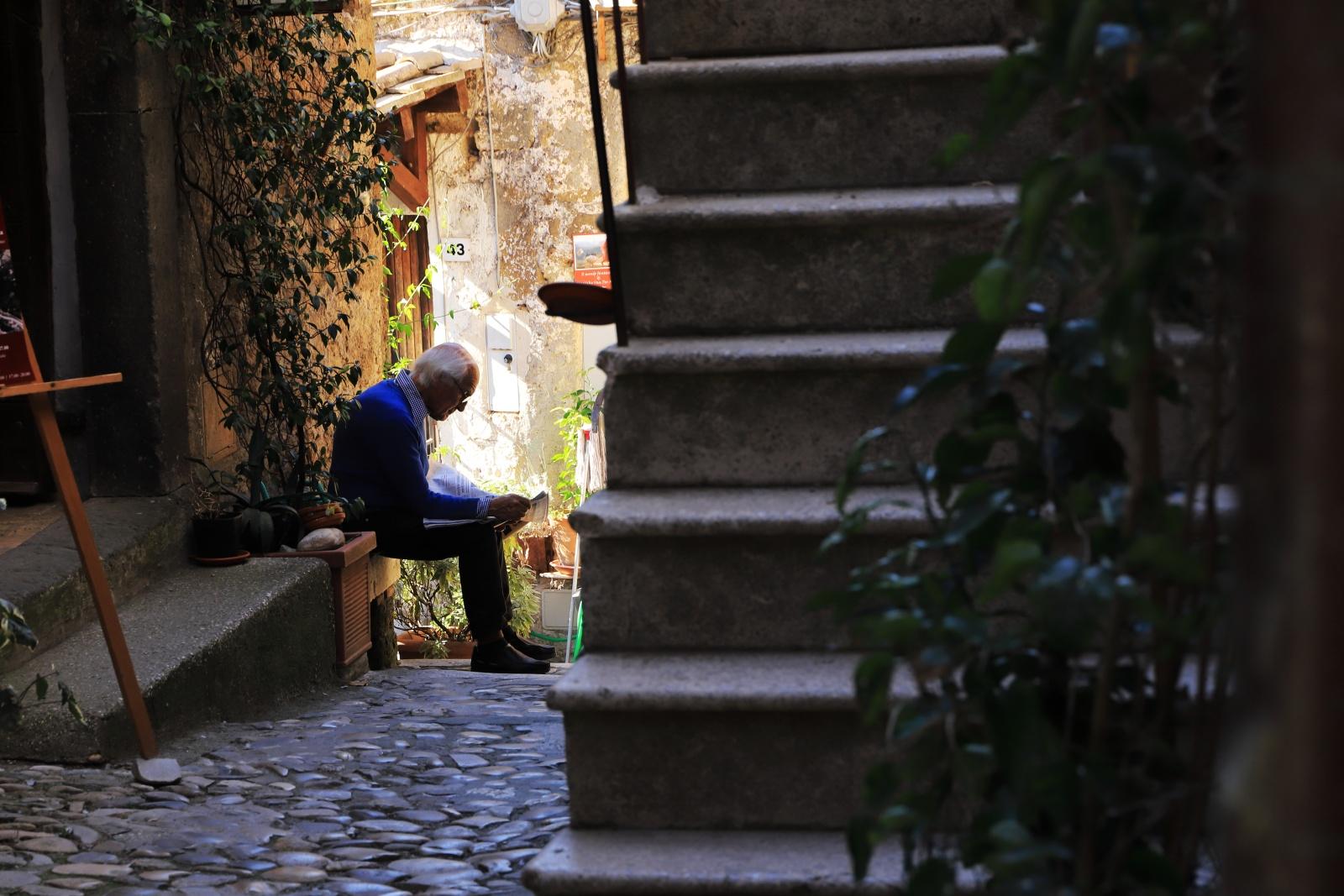 """Borgo-antico - Signore indisturbato legge il giornare nel borgo di calcata.""""Se qualcuno si sentisse infastidito dalla presenza della propria immagine nel mio Reportage puo scrivere a paolocoppola84@gmail.com e provvedero' quanto prima a rimuoverla."""""""